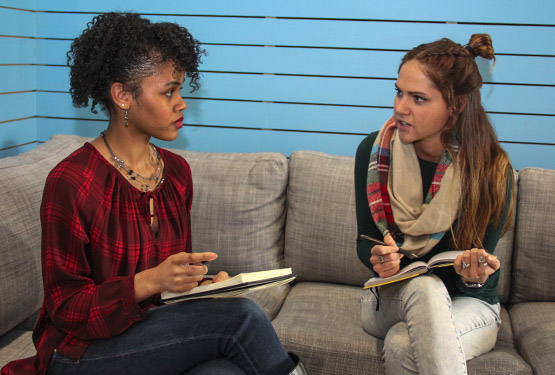Carly and a client, seated on a couch, discuss a project