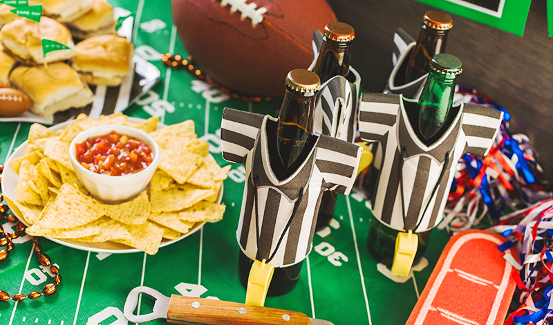 Table spread of Super Bowl party items including salsa and nachos, drinks with referee-outfitted koozies, sliders and pom-poms.
