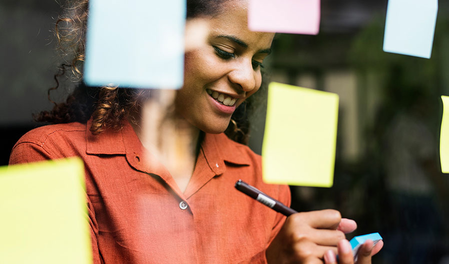 woman writing on sticky notes